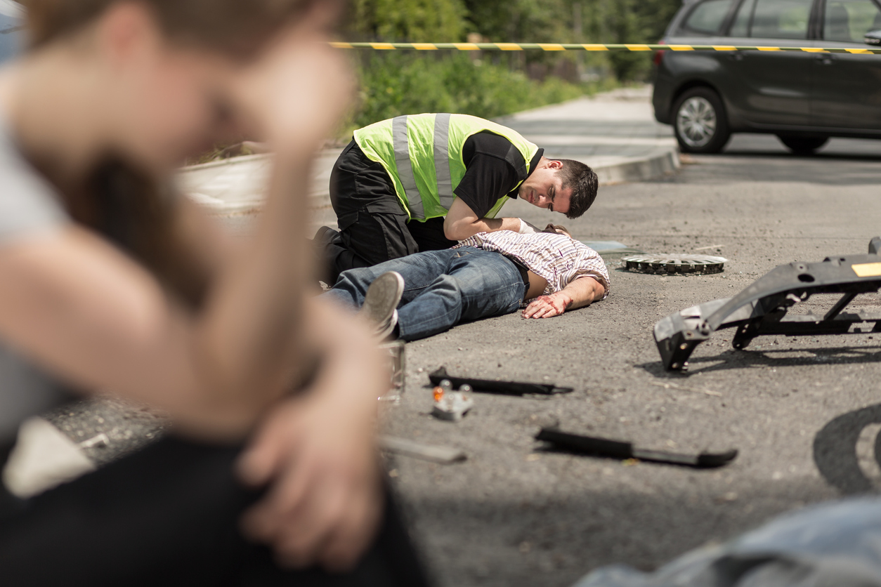 paramedic helping on street man injured in car accident, in the foreground despair woman sitting.