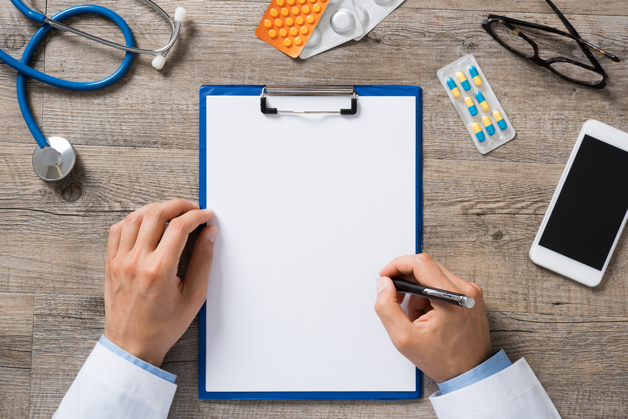 High angle view of doctor hand writing prescription on paper. Doctor filling in empty medical prescription. Top view of hand of doctor writing on blank paper with medicine and capsule on a wooden table. Health and medical concept.